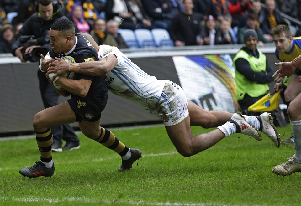 COVENTRY, ENGLAND - FEBRUARY 18: Marcus Watson of Wasps scores their first try despite the efforts of Olly Woodburn of Exeter Chiefs during the Aviva Premiership match between Wasps and Exeter Chiefs at The Ricoh Arena on February 18, 2018 in Coventry, England. (Photo by Henry Browne/Getty Images)